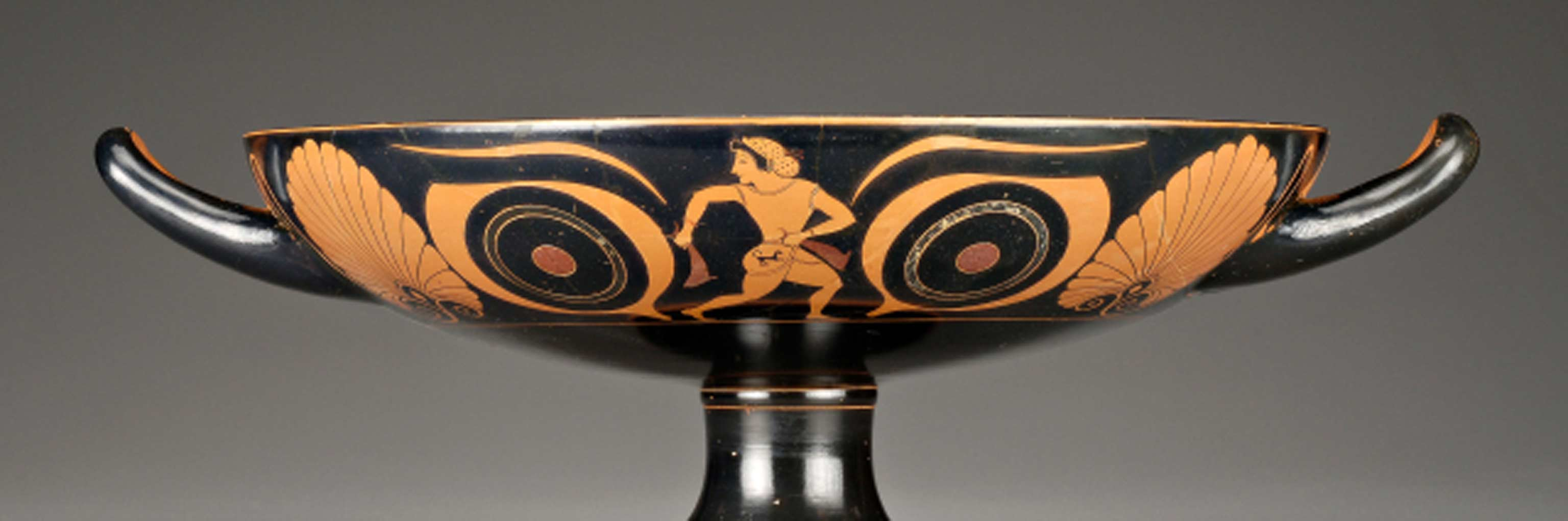 Ancient Greek pot painted with a man centered between two large eyes.
