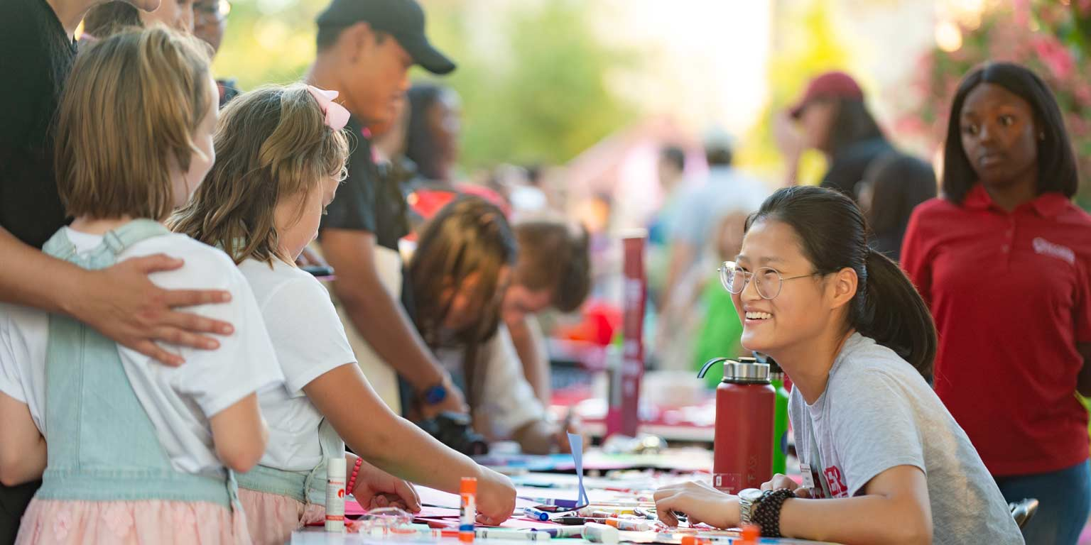 Two young girls visit a table to make art at an Indiana University event.