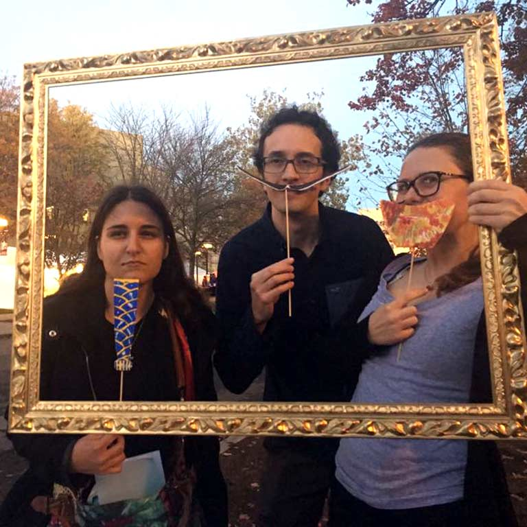 Three students pose with props inside a picture frame.
